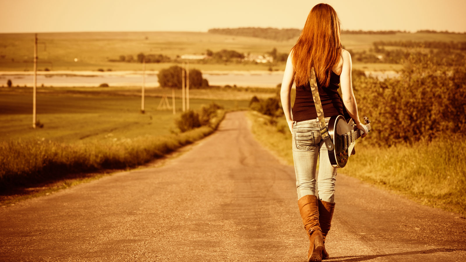 Woman with guitar on the country road